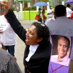 Writer Audrey Matura-Shepherd at May 17 Belize City Rally with photo of Prof. Bain